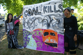 Alison Guzman and Bobo Tsim at the Eugene Celebration Parade. Banner designed and created by Kat Herrera, a Beyond Toxics volunteer (not pictured).