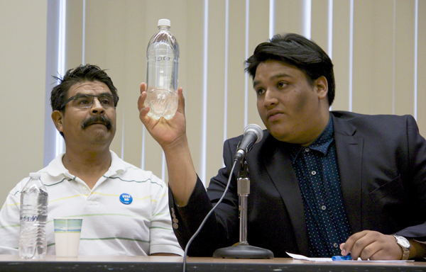 Joel Iboa (right) shows untreated water for labor camp workers in Oregon collected by Dagoberto Morales, Director of UNETE Center for Farmworker Advocacy (left). Photo by Natalie Hardwicke.